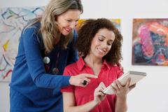 Mid adult woman advising art student drawing in sketch pad in art gallery - stock photo