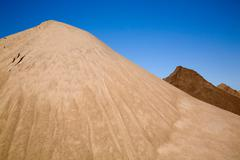 Mound of sand in commerical sand pit - stock photo