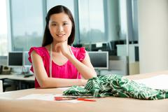 Portrait of young fashion designer at desk Stock Photos