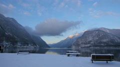 Benches and people on the shore of Hallstatter See on a winter day in Hallstatt Stock Footage