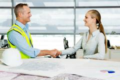 Engineer shaking hands with architect at desk of blueprints in office Stock Photos