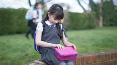 4K Little girl alone in schoolyard cheers up when children come to play Stock Footage