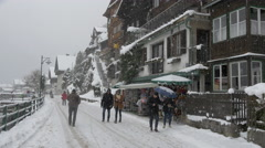 People walking by souvenir stalls on Seestrasse on a winter day, Hallstatt Stock Footage
