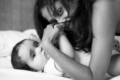 Mother and baby laying on bed Stock Photos