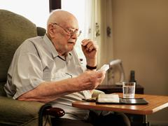 Older man taking medication in armchair Stock Photos