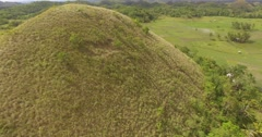 Aerial shot over chocolate hill to reveal more chocolate hills in Bohol - stock footage