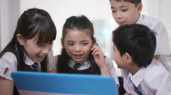 4K Happy group of children looking at computer in school classroom - stock footage