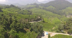 Aerial fly over munnar hills, with a pan up to reveal mountains in Munnar Stock Footage