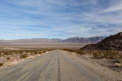 Desert highway leading down into Death Valley National Park - stock photo
