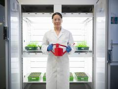 Scientist holding watering can in front of incubator of plant cultures in biolab Stock Photos