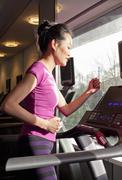 Woman running on treadmill in gym - stock photo