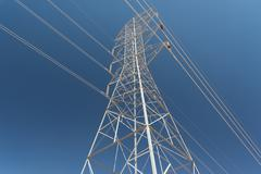 Single high-voltage, high tension power transmission tower, blue sky background Stock Photos