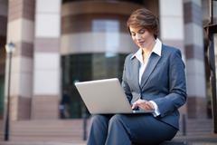 Businesswoman using laptop outdoors Stock Photos