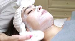 A beautiful woman receiving a facial treatment Stock Footage