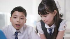 4K Happy little boy & girl looking at computer in school classroom Stock Footage