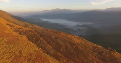 Aerial sunrise view over mountain with hikers and lush tea plantations Stock Footage