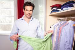 Man hanging up clothes in closet Stock Photos