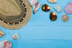 Seashells, hat and sunglasses on blue wooden background Stock Photos