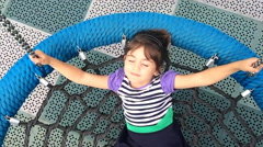 Slow motion of happy girl play on a net swing Stock Footage