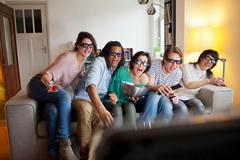 Friends watching 3D movie in living room Stock Photos