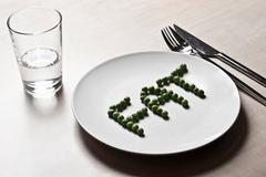 Peas arranged to spell fat on plate Stock Photos