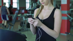 Beautiful blonde on the treadmill uses the phone and listening to music. 4k Stock Footage