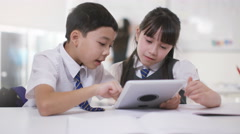 4K Happy little boy & girl looking at computer in school classroom - stock footage