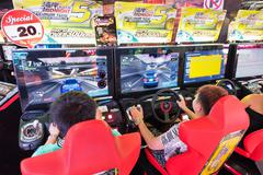 teenagers play in amusement arcade, Bangkok - stock photo