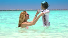 A young mother with her small daughter playing in the turquoise waves of the sea Stock Footage