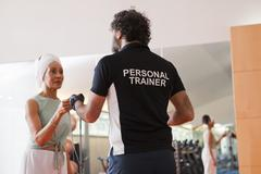 Woman working with trainer in gym Stock Photos