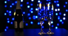 empty glasses and bottle of champagne on the blue boke background - stock footage