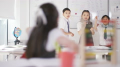 4K Portrait little girl at her desk in classroom with friends in background Stock Footage