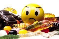 Sad Emoticon Eating Sweets - stock photo