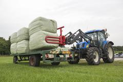 Agriculture loading of plastic hay bales. - stock photo