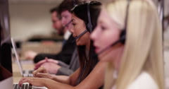 4k, A team of call centre executives wearing headset busy on a phone - stock footage