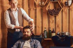 Positive barber drying hair of his client with towel - stock photo