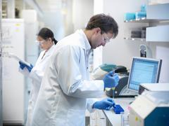 Scientists conducting the process of Polymerase chain reaction (PCR) to amplify Stock Photos