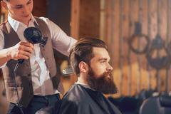 Professional barber styling hair of his client - stock photo