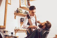 Professional barber cutting beard of handsome man Stock Photos