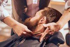 Professional barber shaving beard of his client - stock photo