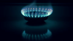 Burning gas in a kitchen stove and its reflection from the surface of the device Stock Footage