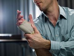 Businessman wearing wrist brace Stock Photos