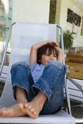 Boy relaxing in deck chair on patio - stock photo