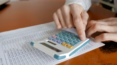 Accounting uses the calculator to check customer lists - stock footage
