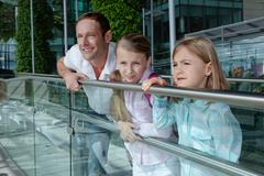 Father with two daughters leaning on railing - stock photo