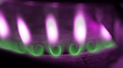 Burning gas in kitchen stove. The tips of the flames painted pink color. Macro - stock footage
