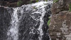 Small waterfall flowing over rocks Stock Footage