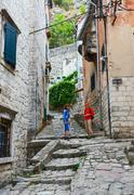 Tourists climb along narrow street of Old town, Kotor, Montenegro - stock photo
