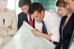 Multi racial businesspeople discussing blueprint Stock Photos