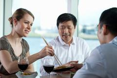 Multi racial businesspeople eating meal Stock Photos